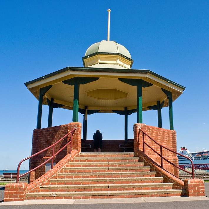 Port Melbourne bandstand rotunda provides a viewing platform over the Bay towards the Pier with the Spirit of Tasmania docked