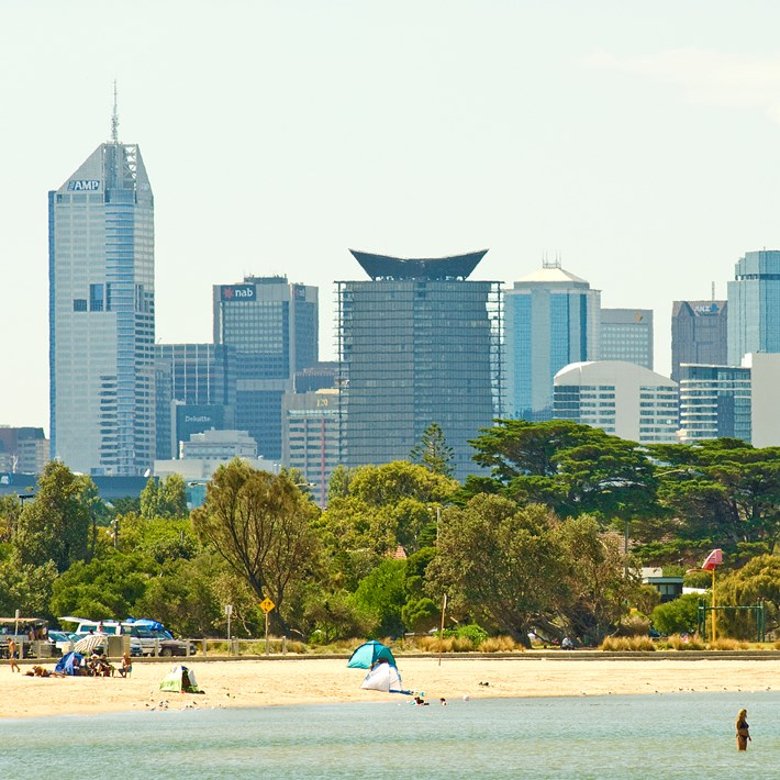 People in the water and enjoying Sandridge Beach with the City skyline in the distance