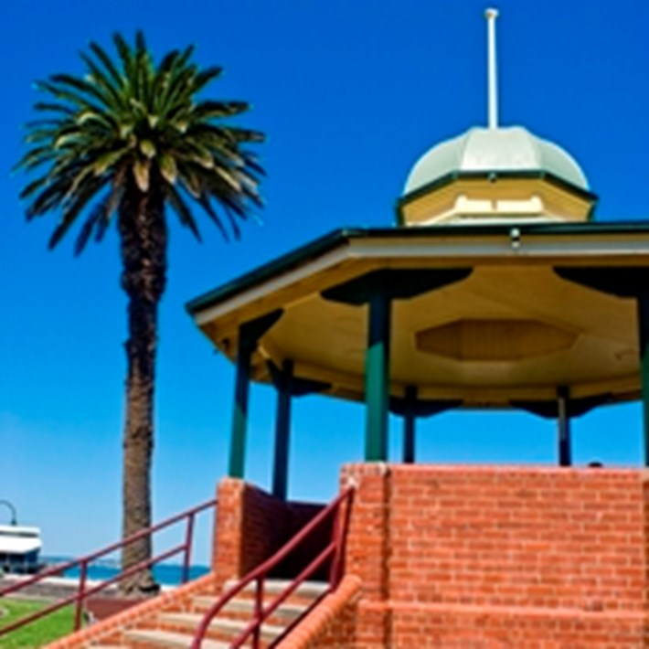 Port Melbourne Bandstand Rotunda with palm tree and Port Melbourne beach in the background